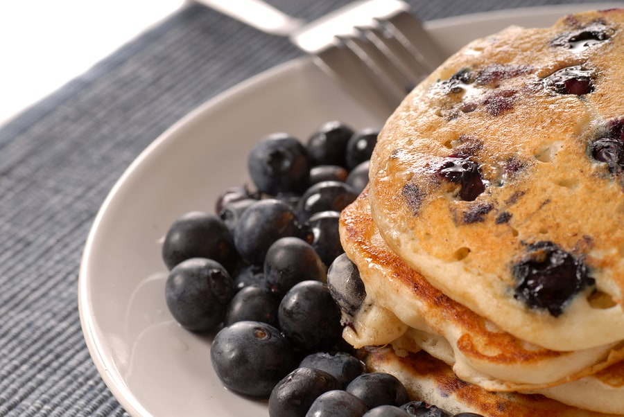 A plate of pancakes with fresh blueberries and syrup